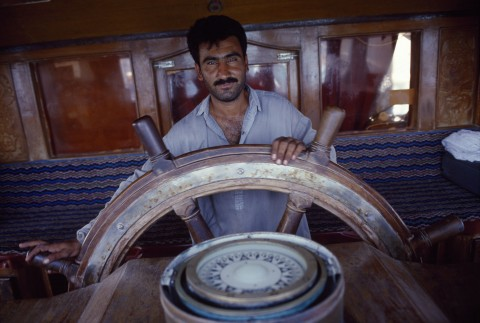 "Helmsman. One after another, each seaman of the ""Fate Al Rahman"" steers the dhow ."
